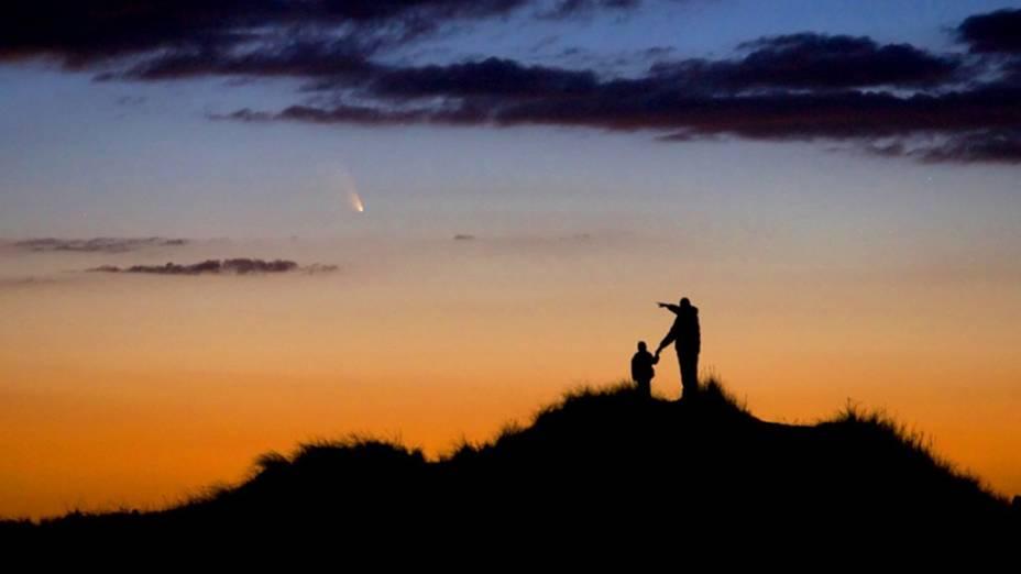 <p>Pai e filho observam a passagem do cometa Pan-STARRS na First Encounter Beach (Praia do Primeiro Encontro, em tradução livre), em Massachusetts, nos Estados Unidos</p>