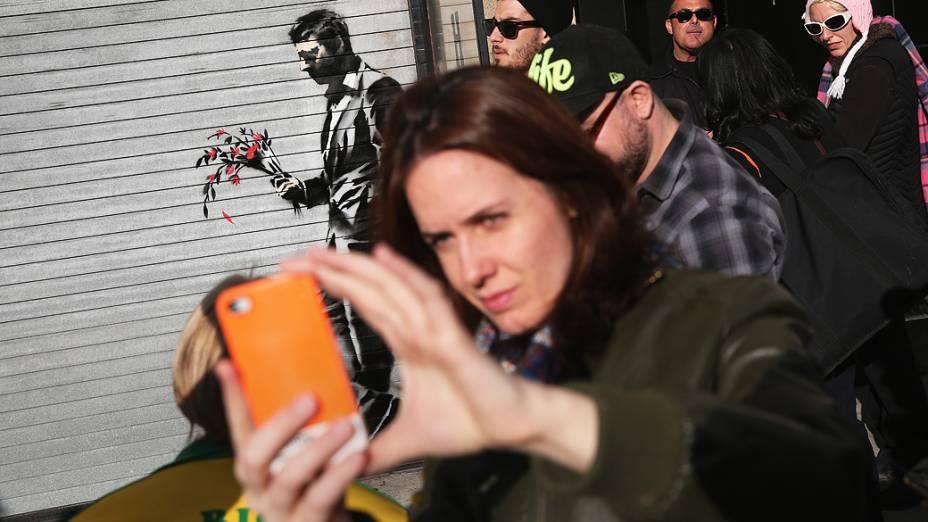 Selfie em frente a pintura do artista britânico Banksy na entrada principal Hustler Club Larry Flint, em Nova York