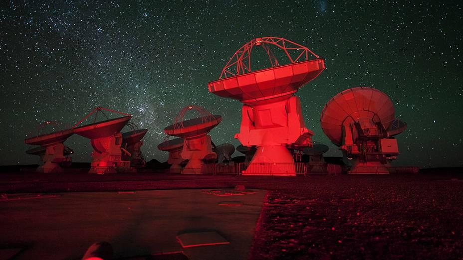 <p>Nesta imagem, as antenas do ALMA aparecem banhadas em luz vermelha. Ao fundo, é possível ver a Via Láctea</p>