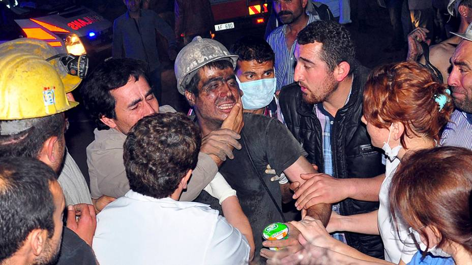Um mineiro resgatado é fotografado enquanto médicos, parentes e colegas de trabalho prestam socorro