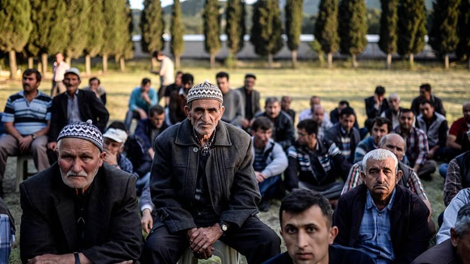 Parentes e amigos de vítimas são fotografados no cemitério de Manisa onde sepulturas foram escavadas para o funeral dosmineiros mortos na explosão de uma mina na província turca ocidental de Soma