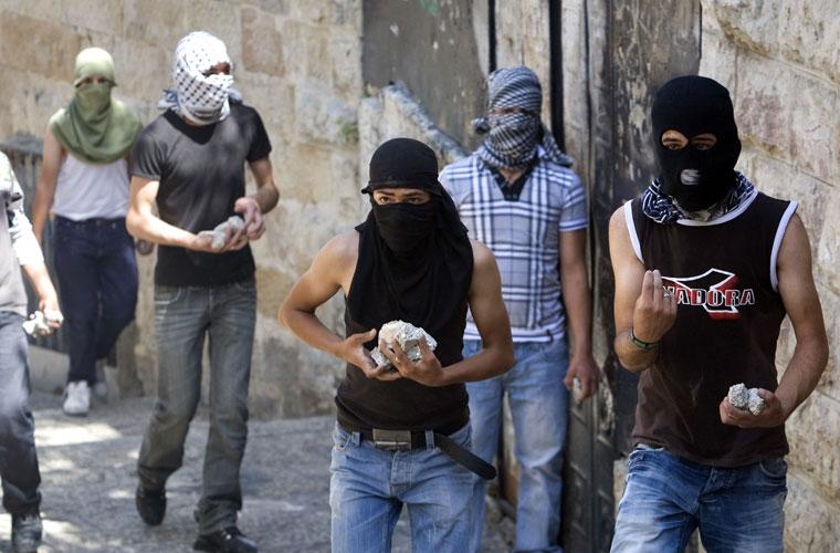 Palestinos se armam com pedras para enfrentar soldados israelenses, em Jerusalém.