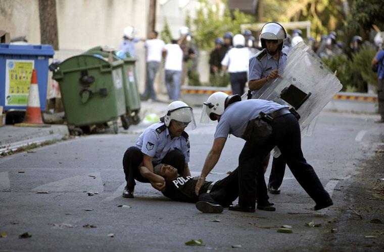 Policiais socorrem manifestante palestino que se feriu durante protesto.