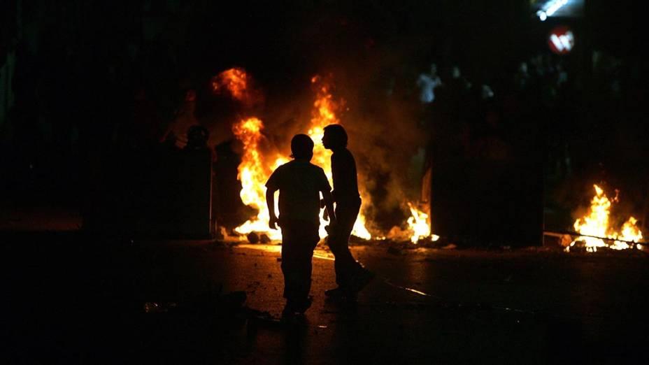 Manifestantes palestinos em frente a sede das forças de segurança palestinas, na Cisjordânia