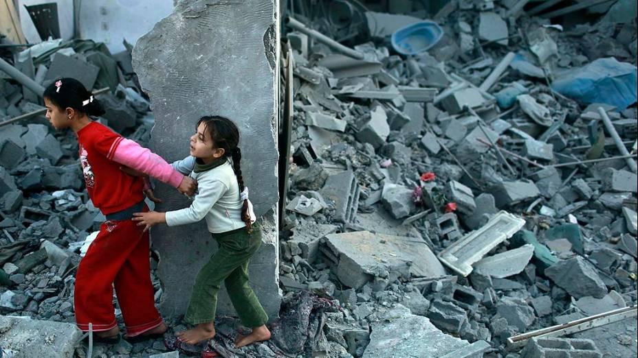 Meninas andam sobre escombros na Faixa de Gaza