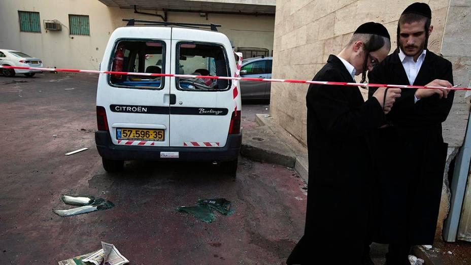 Israelenses ao lado de veículo danificado por foguete lançado por militantes palestinos