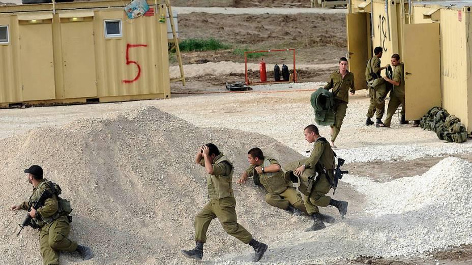 Soldados israelenses correm para se enconder após alerta de sirene, em Ashdod