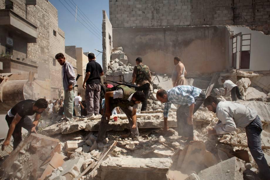 Civis e integrantes do Exército Sírio Livre procuram corpos nos escombros de uma casa destruída por duas bombas da Força Aérea Síria, que tinham como alvo um centro de comando rebelde