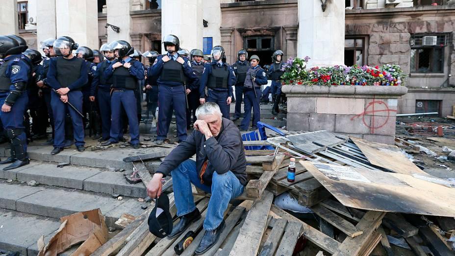 Homem é observado por membros das forças de segurança durante um comício fora do edifício sindical ucraniano que pegou fogo ontem (2) em Odessa, na Ucrânia
