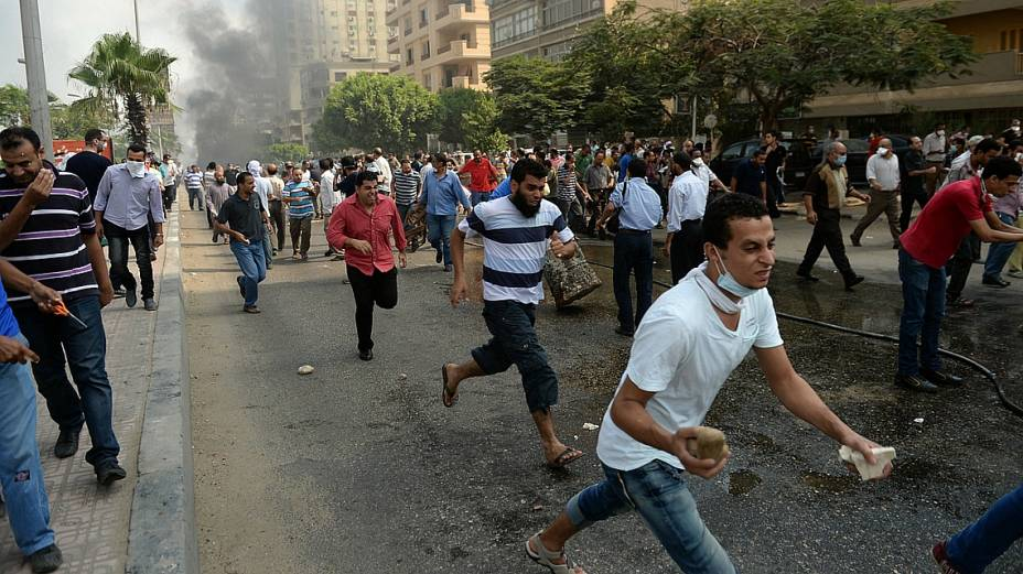 Manifestantes correm após tropas policiais iniciarem ofensiva para dispersar protesto pró-Mursi