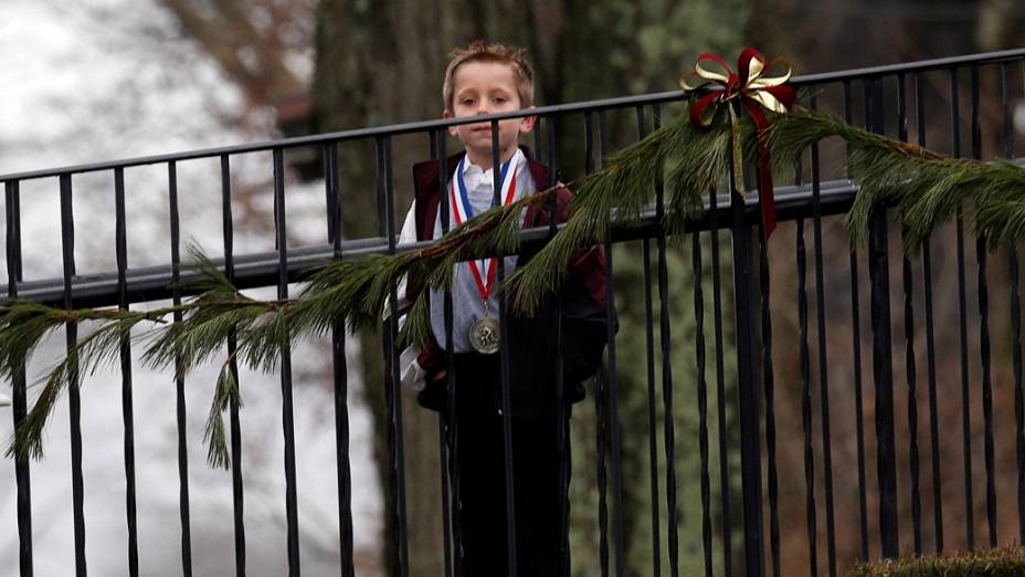 Menino espera para entrar no local, onde a família do garoto Jack Pinto, de seis anos, morto no ataque à escola primária Sandy Hook,  realiza seu funeral, em Newtown, Connecticut