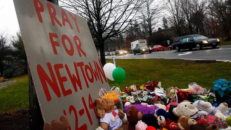 Carro fúnebre carregando o caixão do garoto Jack Pinto de seis anos, passa por um memorial improvisado no caminho para o cemitério de Newtown
