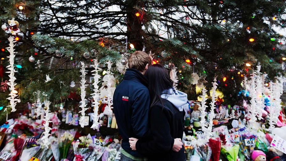 Casal se abraça ao visitar memorial para as vítimas do tiroteio da escola primária Sandy Hook em Newtown
