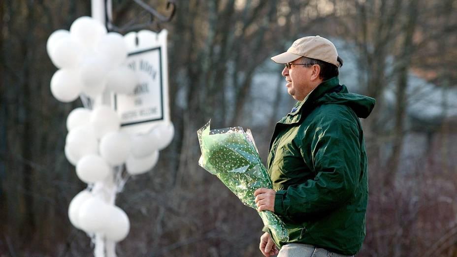 Habitante da cidade de Newtown leva flores para a frente da escola primária Sandy Hook, onde pelo menos 27 pessoas foram mortas nesta sexta