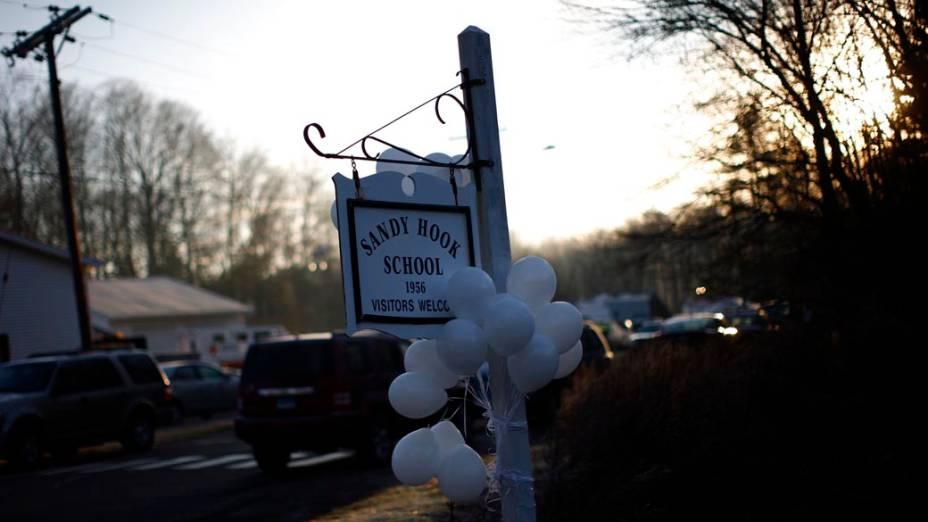 Balões pendurados na placa da escola Sandy Hook, onde aconteceu o tiroteio que matou 27 pessoas nessa sexta, em Newtown