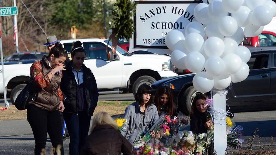 Moradores da cidade de Newtown prestam homenagens às vítimas do tiroteio, em frente a escola Sandy Hook