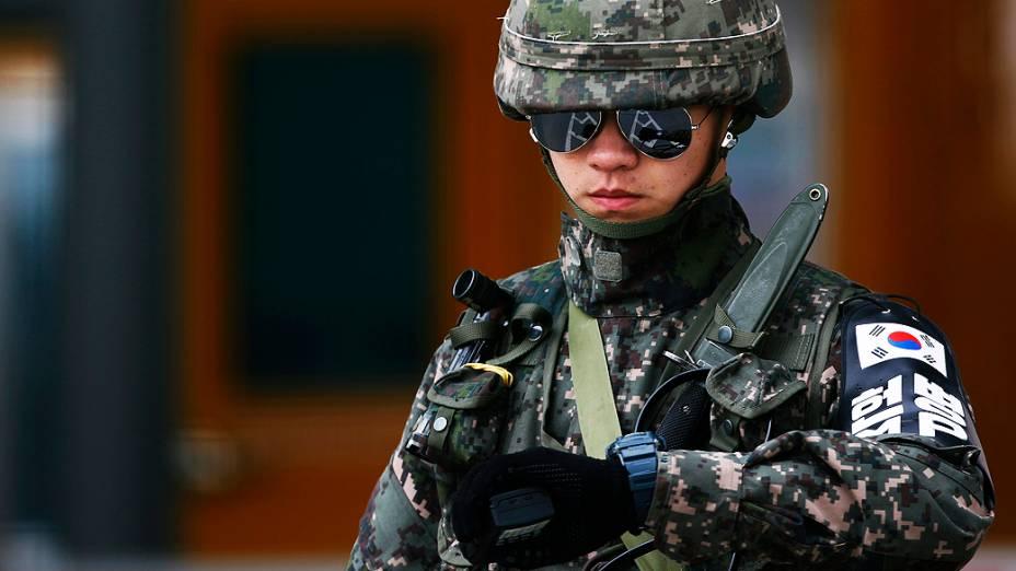 Soldado sul-coreano checa o horário de chegada de veículos trazendo trabalhadores do complexo industrial de Kaesong, localizado na Coreia do Norte, no posto sul-coreano de fronteira em Paju