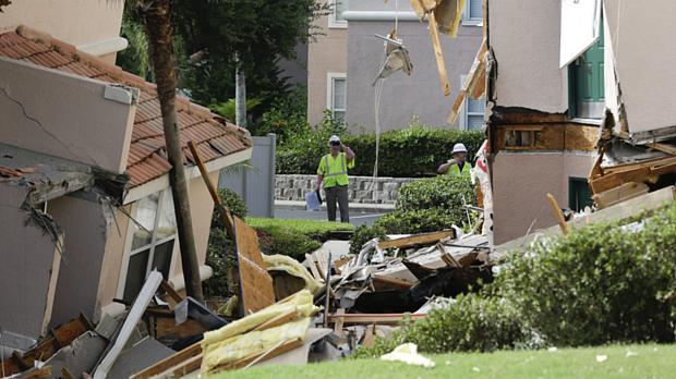 Inspetores observam danos provocados por buraco que destruiu construções em Clermont, na Flórida