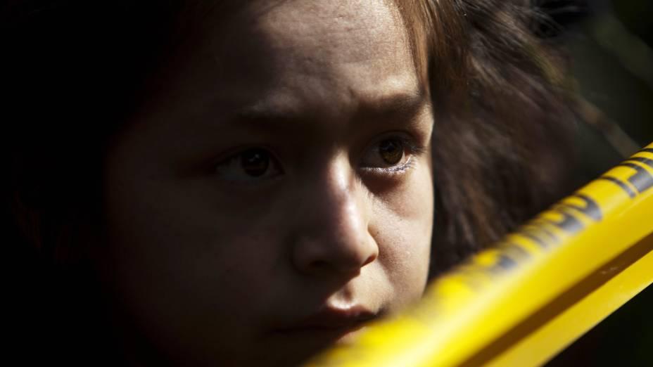 Criança observa local onde sete pessoas da mesma família, incluindo duas crianças, foram mortas a tiros, no vilarejo de Las Escobas, nos arredores da Cidade da Guatemala