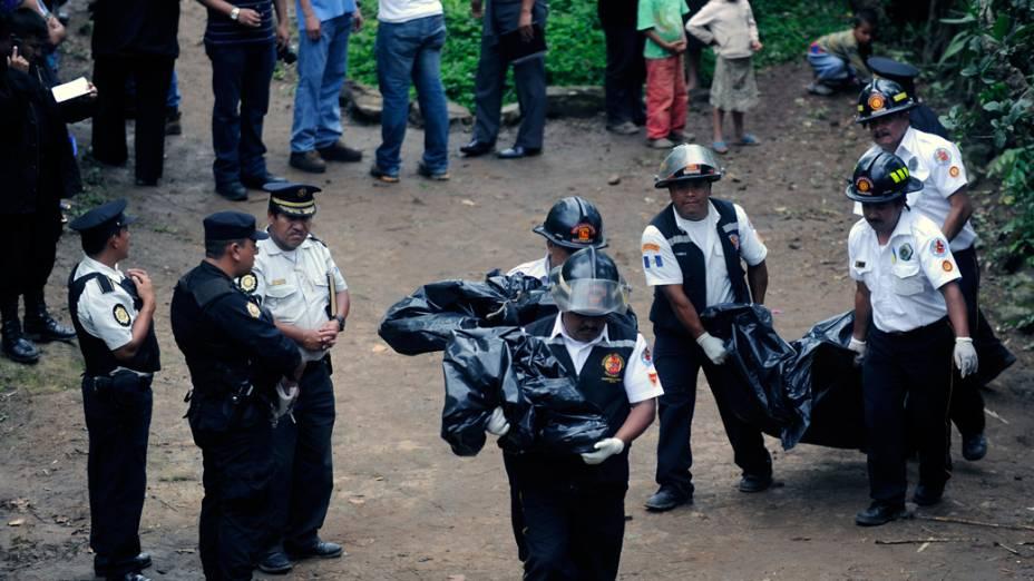 Bombeiros carregam os corpos de sete pessoas da mesma família que foram assassinadas em Las Escobas, Guatemala