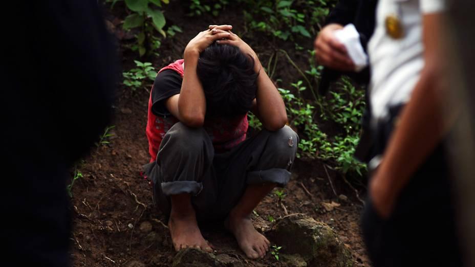 Criança que conseguiu escapar de um ataque contra sua família é protegida por policiais no vilarejo de Las Escobas, nos arredores da Cidade da Guatemala, onde o crime ocorreu