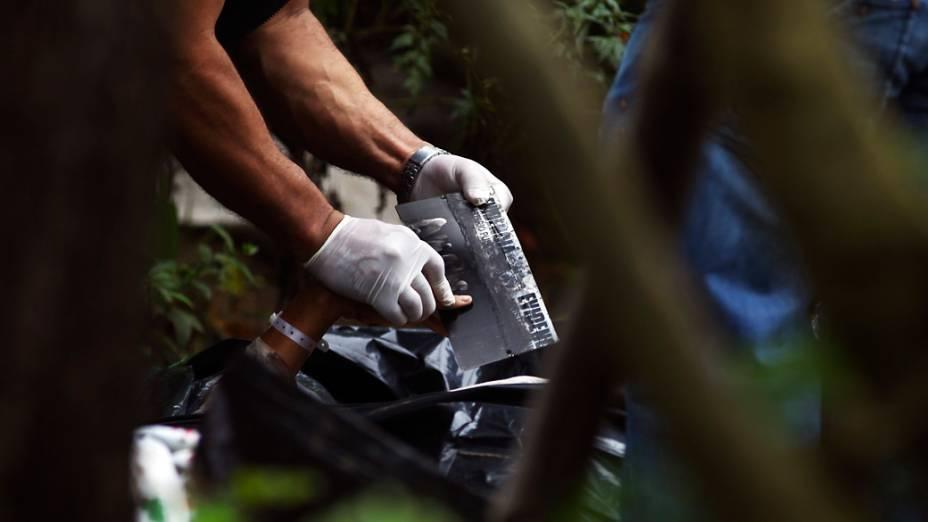 Equipe de perícia recolhe impressões digitais. Sete pessoas de uma mesma família foram assassinadas em Las Escobas, Guatemala