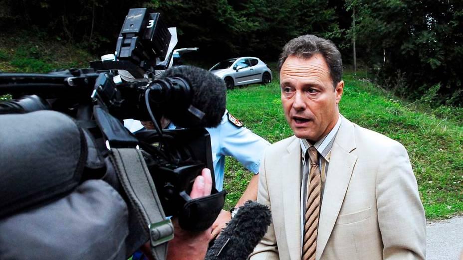 Promotor do Annecy responde a perguntas dos jornalistas na estrada que leva para a cena do crime