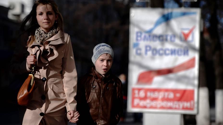 Em Simferopol, ucranianos passam por placa do referendo que acontece em 16/03/2014