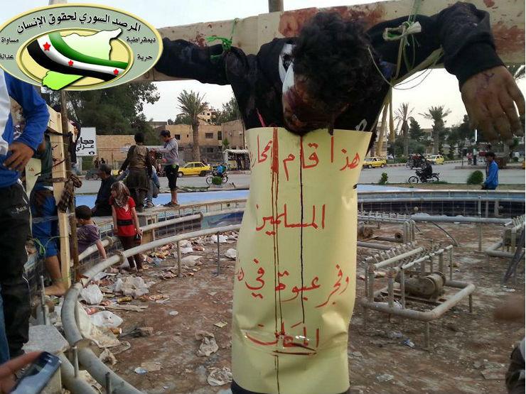 Pesssoas observam um homem morto e crucificado em Raqqa, na Síria