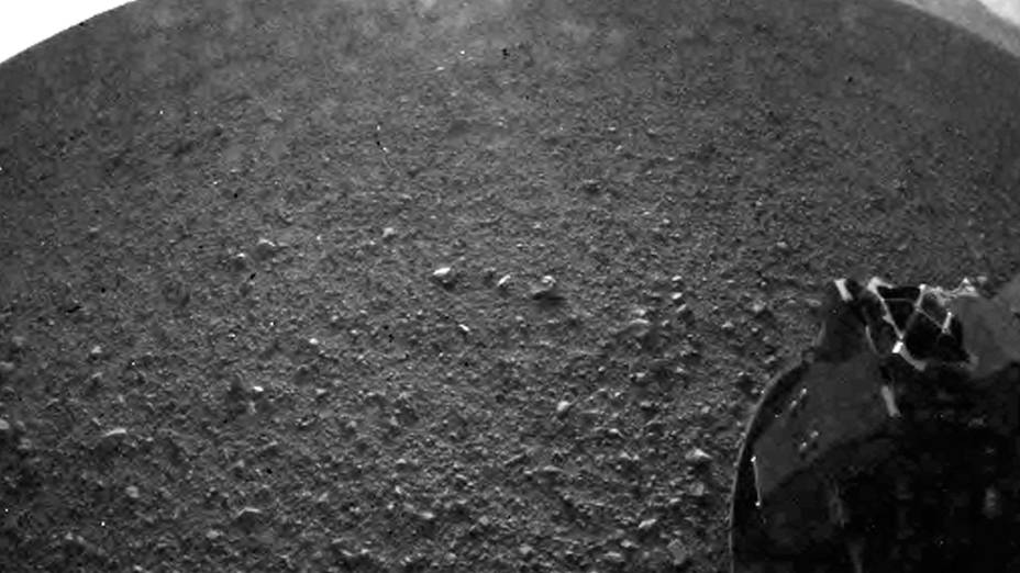 <p>Primeira imagem feita pelo Curiosity em Marte mostra a roda do jipe-robô sobre o solo de Marte</p>