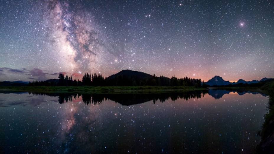<p>Via Láctea refletida no rio Snake, no Parque Nacional de Grand Teton, nos Estados Unidos</p>
