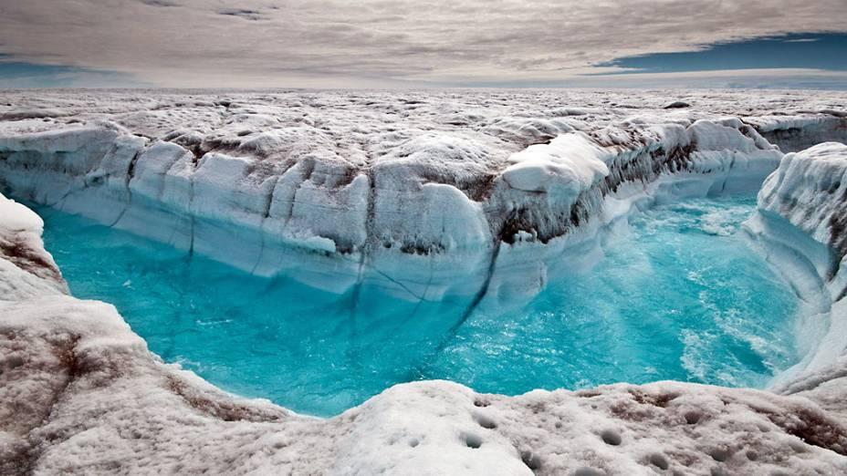 A água derretida corre na superfície da calota polar da Groenlândia, formando canais na superfície