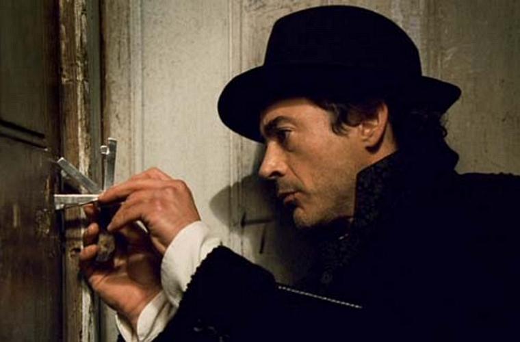 Em <em>Sherlock Holmes</em>, como o famoso detetive em uma adaptação moderna da obra de Conan Doyle.