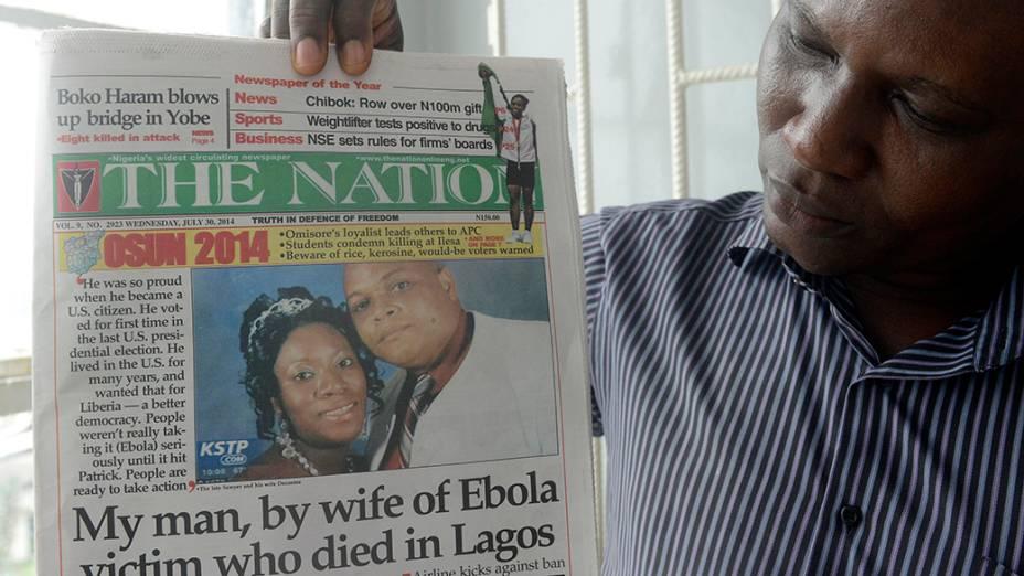 Homem segura jornal com imagem do diplomata liberiano Patrick Sawyer, morto pelo vírus ebola na cidade de Lagos, na Nigéria