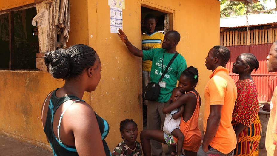 Na Libéria, agente de saúde da informações sobre a prevenção do vírus Ebola