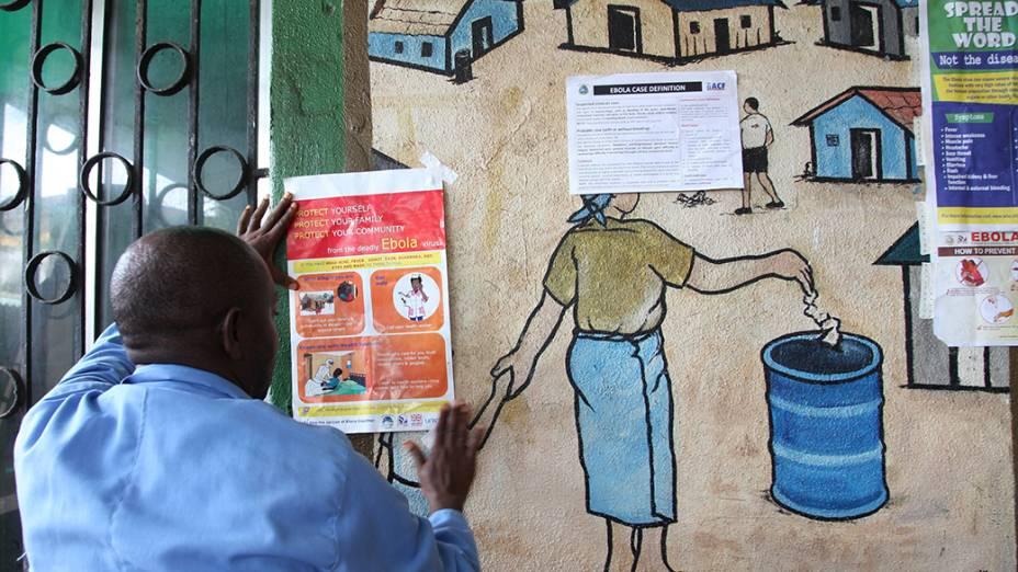 Homem cola informativo sobre o vírus ebola, na Libéria