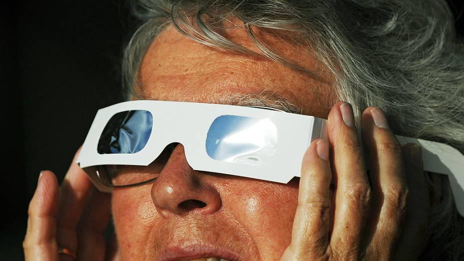 Turista observa eclipse total do Sol na cidade de Palm Cove, na Austrália