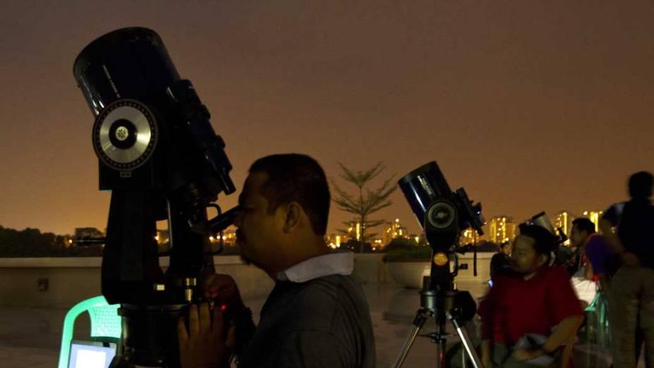 <p>Pessoas observam o eclipse lunar na cidade de Putrajaya, Malásia</p>