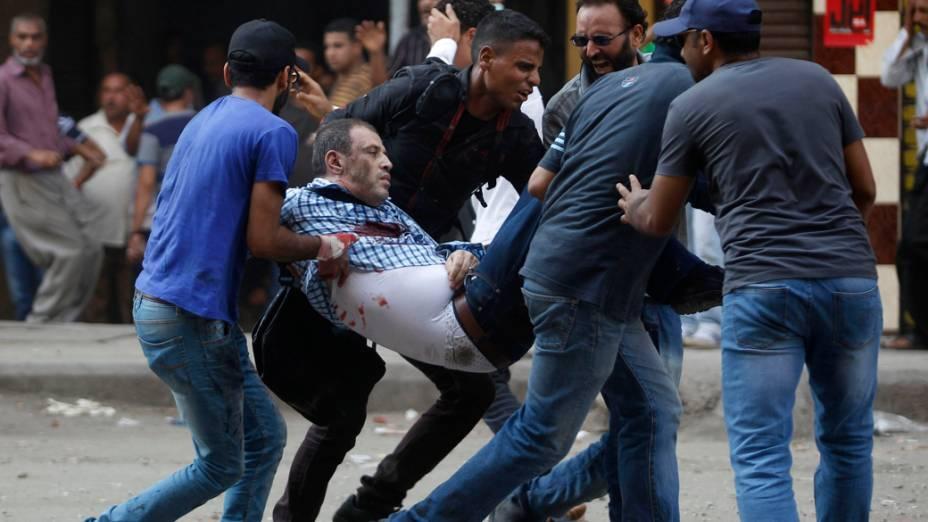 Partidários do presidente deposto egípcio Mohamed Mursi socorrem um manifestante ferido durante confrontos na Praça Ramsés, no Cairo