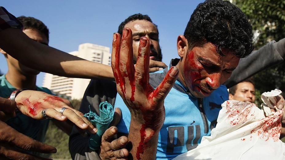 Manifestantes ajudam homem ferido durante conflitos nesta sexta-feira (14), perto da praça Tahir, no Cairo, capital do Egito. Eles protestavam contra filme considerado ofensivo ao Islã