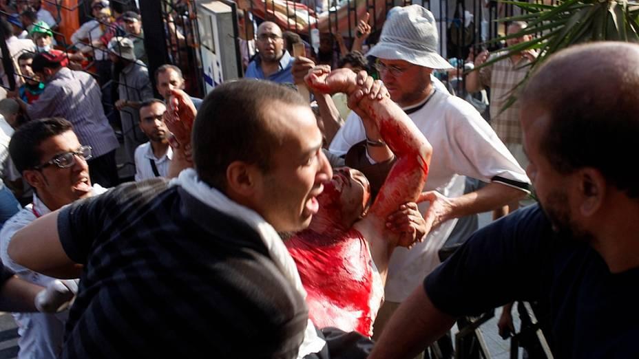 Islamita é carregado após ser alvejado durante confronto com soldados no Cairo