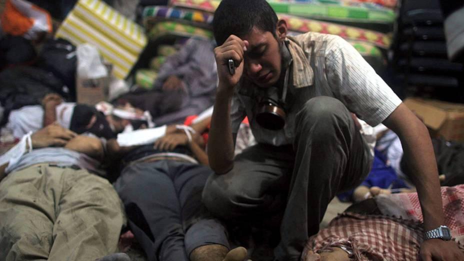 Um homem chora em meio aos corpos dispostos em um necrotério depois que as forças de segurança egípcias atacaram dois acampamentos onde partidários do presidente deposto Mohamed Mursi estavam acampados no Cairo, nesta quarta feira (14/08/2013)