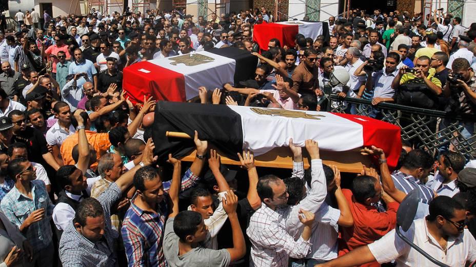 Parentes e amigos de policiais que foram mortos durante os confrontos de quarta-feira (14) carregam caixões cobertos com bandeiras do Egito durante um funeral militar no Cairo - (15/08/2013)