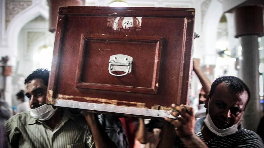 Homens carregam caixão de manifestante morto durante os confrontos com a polícia na quarta-feira (14) durante um funeral no Cairo - (15/08/2013)
