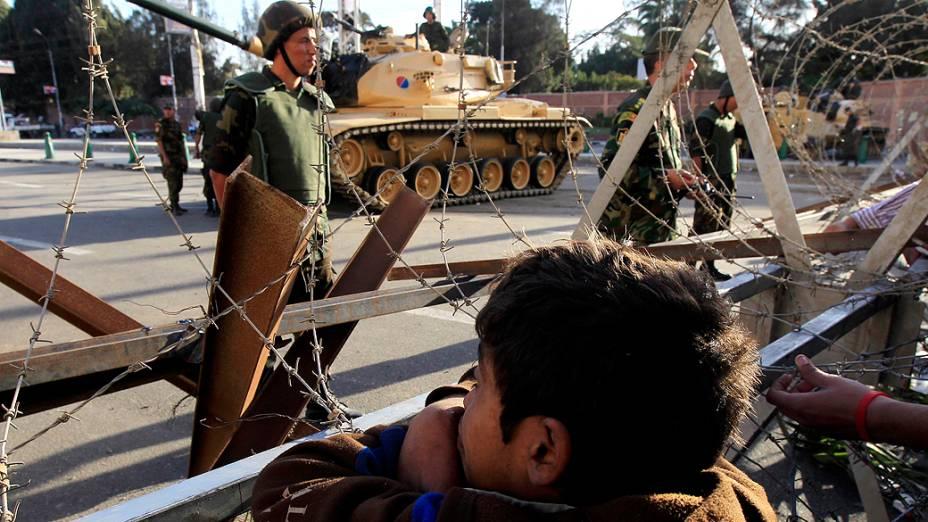 Menino observa, pelo arame farpado, os militares que protegem os arredores do palácio presidencial no Cairo, Egito
