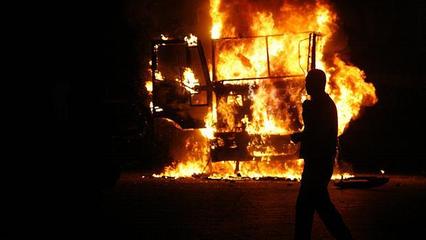 Homem passa em frente a carro de polícia incendiado durante protesto