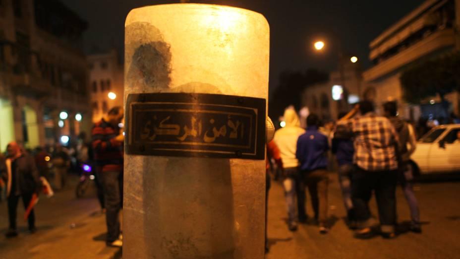 Manifestante carrega escudo da polícia de choque durante protesto em frente ao palácio presidencial, no Cairo