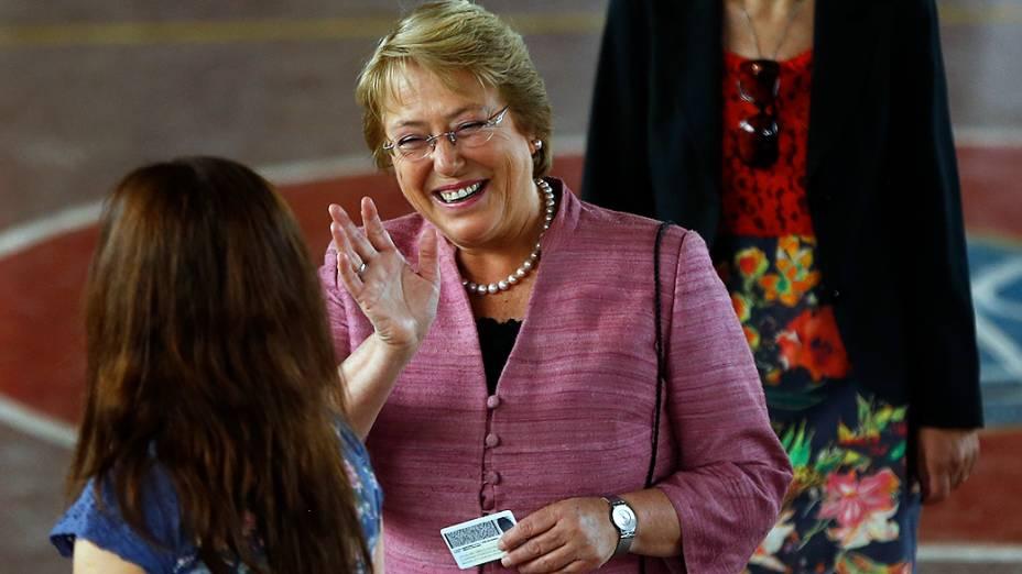 Michelle Bachelet cumprimenta funcionários da seção eleitoral onde votou em Santiago, neste domingo (17)