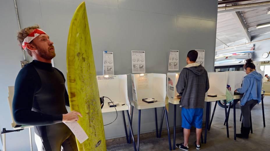 Eleitor vota com uma prancha de surfe e vestindo uma roupa de lycra em Venice Beach, na Califórnia