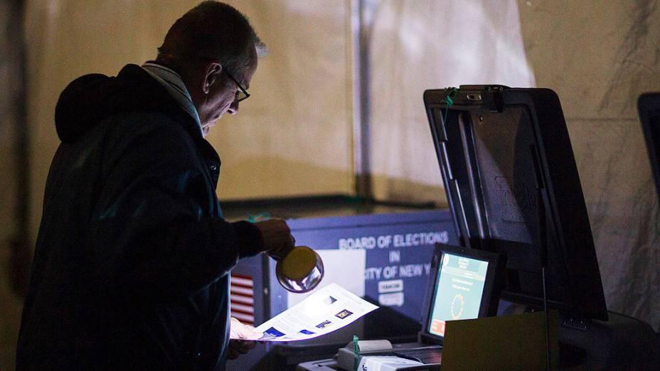 Eleitor procura por nomes de candidatos no escuro no bairro do Queens, em Nova York